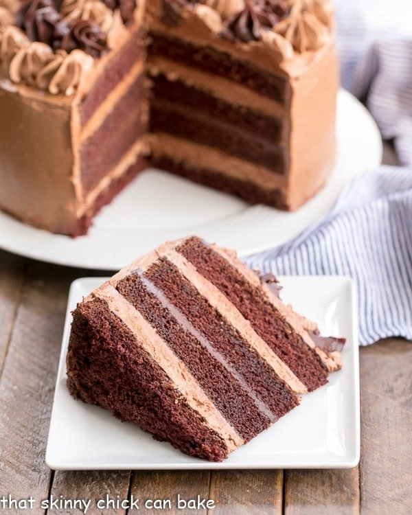 Chocolate Fudge Layer Cake with a slice on a square white plate with cut cake in the background