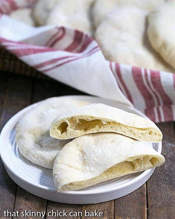 Homemade Pita Bread on a white ceramic plate with once sliced in half
