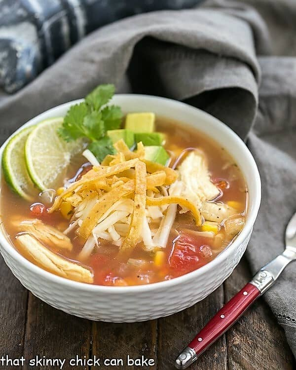 Leftover Turkey Tortilla Soup  in a white bowl garnished with lime and cilantro sprigs