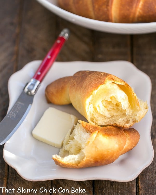 Buttery Homemade Crescent Rolls on a white plate with a red handled knife