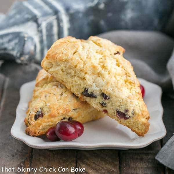 Cranberry Eggnog Scones on a square plate with fresh cranberries