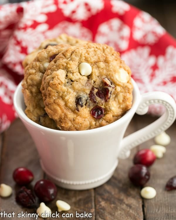 Gingered Cranberry Oatmeal Cookies in a white coffee cup with cranberries and white chocolate chips