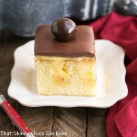 Boston Cream Pie Poke Cake | A moist, buttery cake filled with vanilla pudding and topped with ganache!