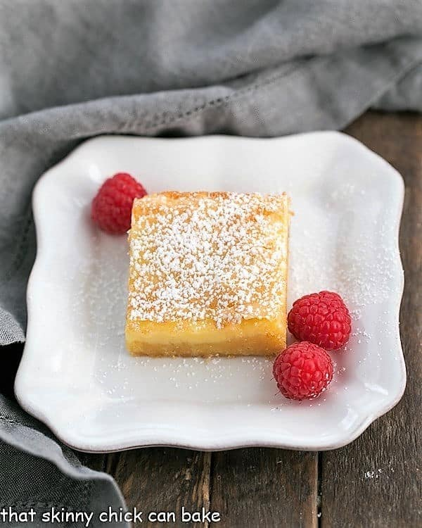 Gooey Butter Bars dessert on a plate with fresh raspberries