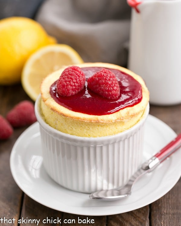 Raspberry Topped Lemon Soufflés in a white ramekin on a saucer with a red handled spoon