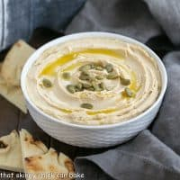 a white bowl filled with creamy hummus from scratch
