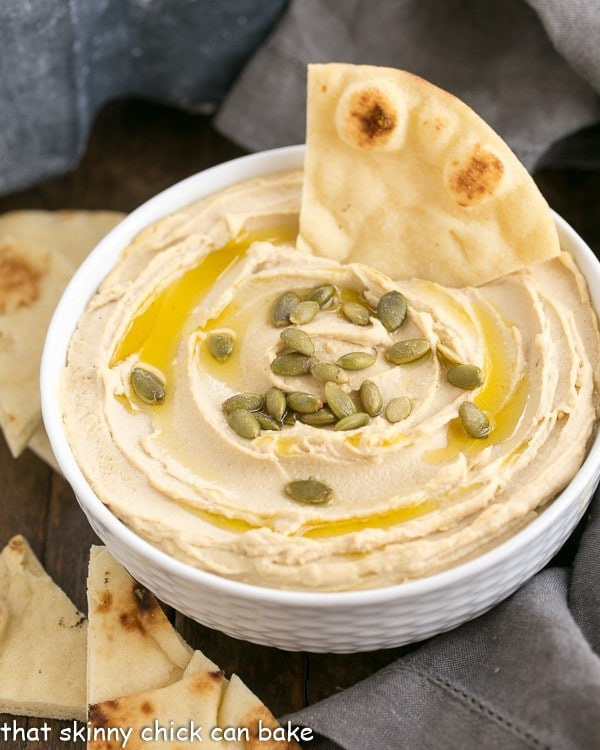 a white bowl of creamy hummus from scratch, garnished with pepitas and a drizzle of olive oil