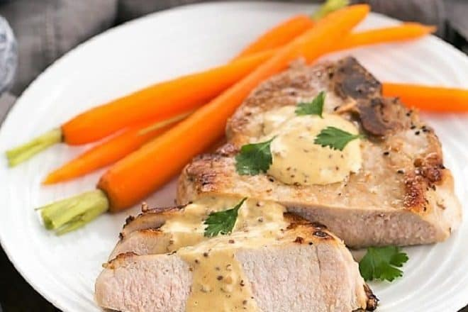 Pork Chops Dijonnaise on a white plate with carrots