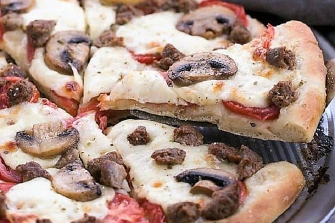 Sausage Mushroom Pizza with slice being removed from a pizza pan