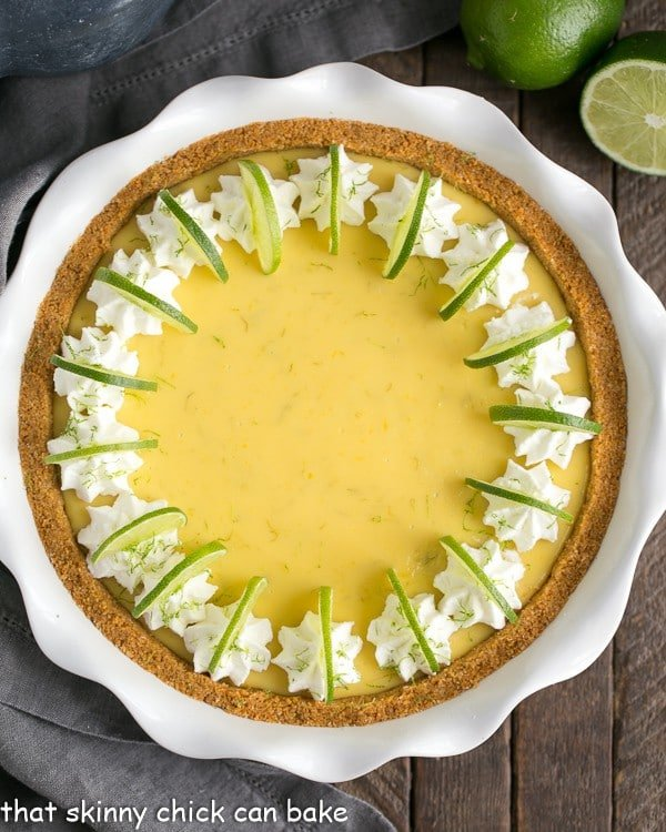 Key Lime Pie with Graham Cracker Crust in a white ceramic pie plate garnished with lime slices and whipped cream