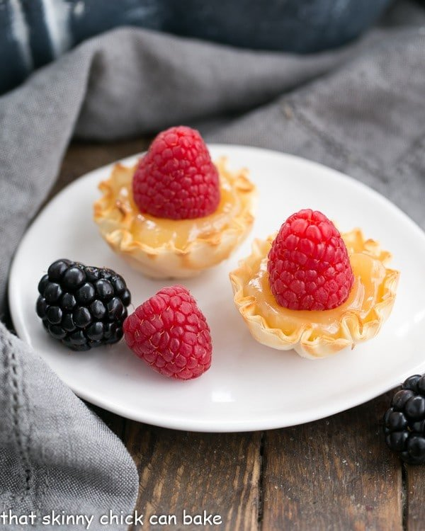 Mini Lemon topped with raspberries on an oval white plate