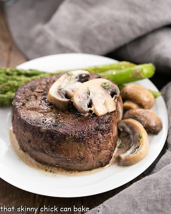 Mushroom Topped Pepper Steak topped with mushrooms on a white plate with asparagus spears