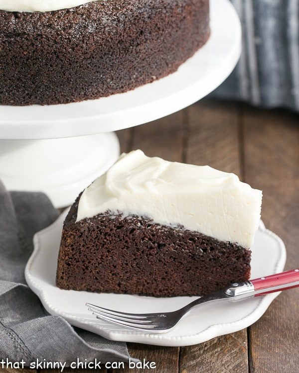 slice of Chocolate Guinness Cake on a white dessert plate with a fork next to the cake