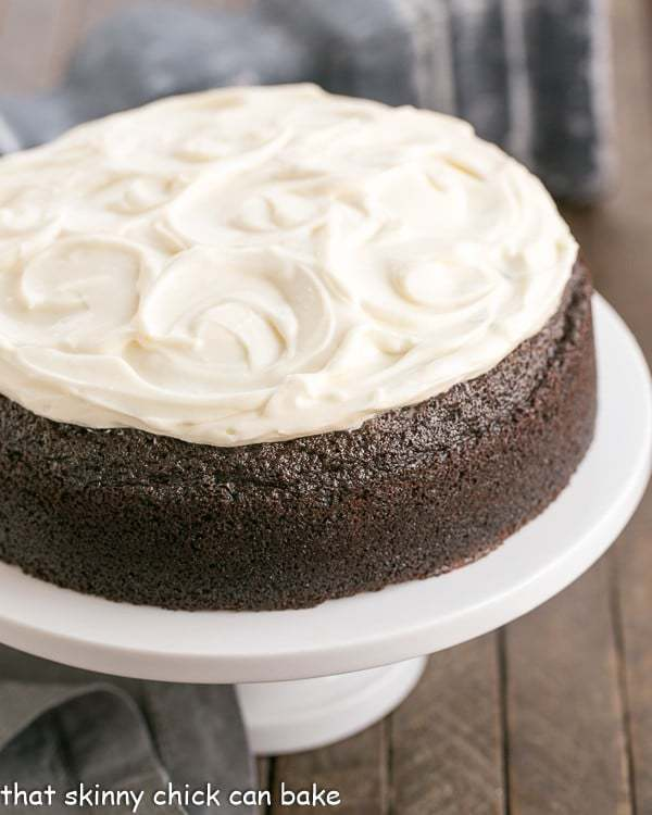 chocolate Guinness cake topped with cream cheese icing on a white cake stand