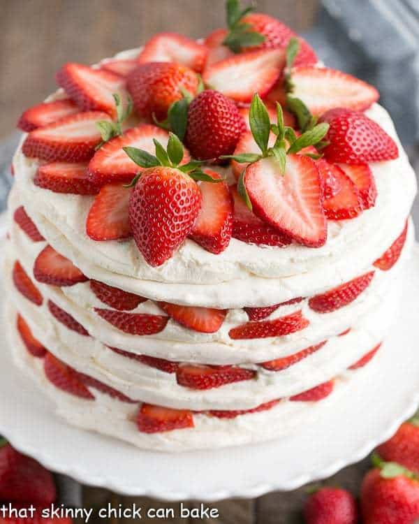 Fresh Strawberry Meringue Cake on a white cake plate. The cake is garnished with a pile of sliced fresh strawberries on top