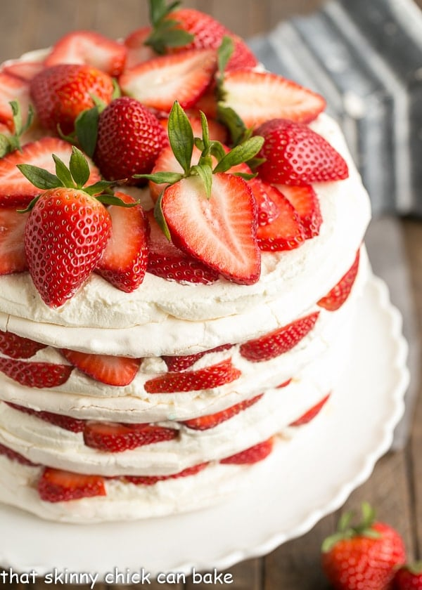 Side view of Fresh Strawberry Meringue Cake on a white porcelain cake stand