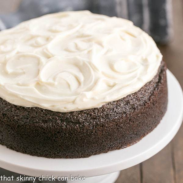 Chocolate Guinness Cake topped with cream cheese frosting on a white cake stand