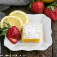 white dessert plate with the Best Lemon Bars, garnished with a fresh strawberry and lemon slices