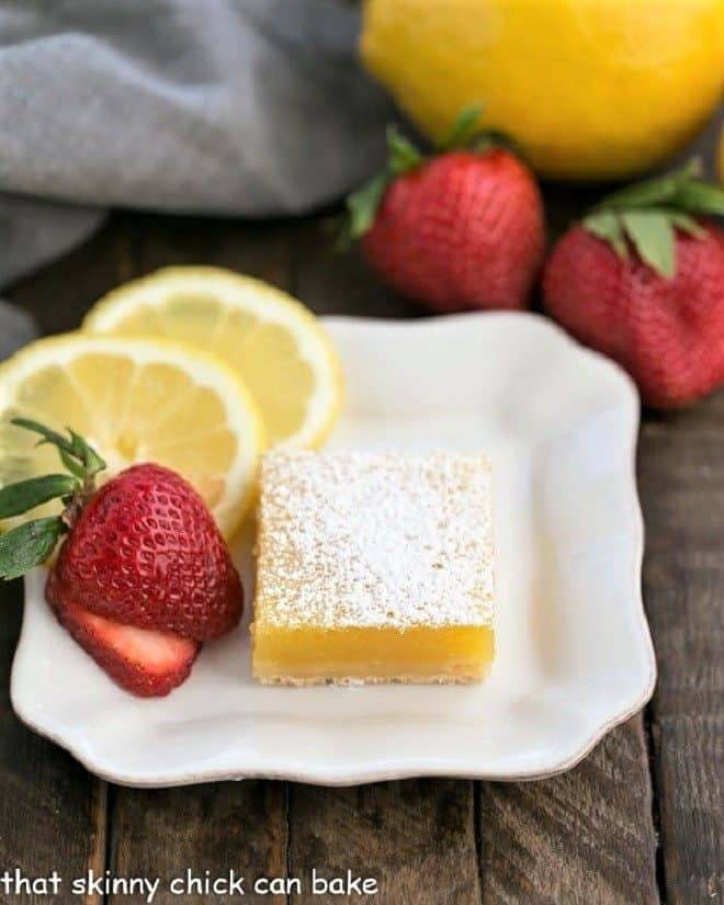 White dessert plate with the Best Lemon Bars, garnished with fresh strawberry slices and slices of lemon