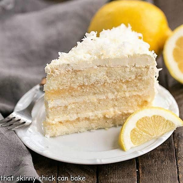 Lemon Layer Cake with Lemon Curd Filling slice on a white ceramic plate with a lemon wedge