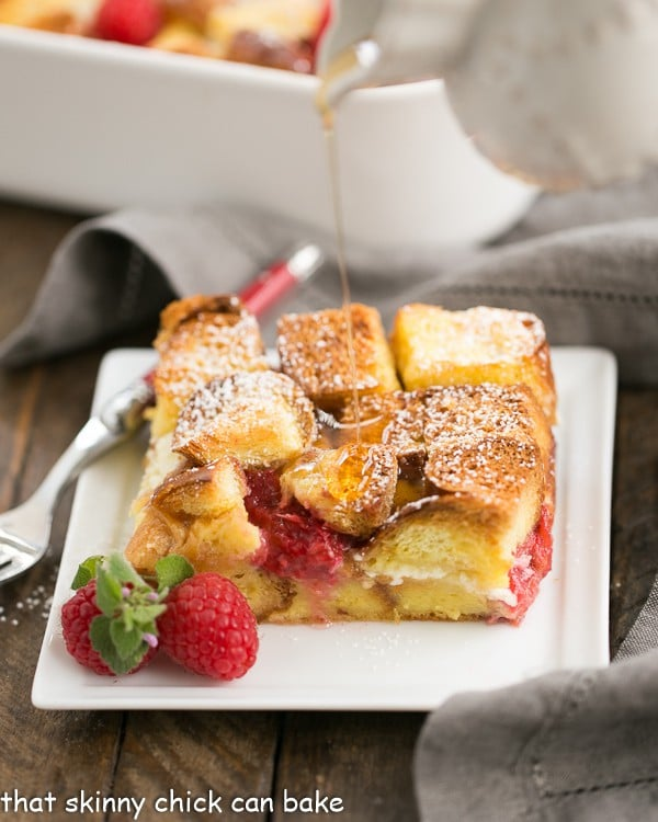 Raspberry Mascarpone French Toast Casserole on a white plate with a drizzle of maple syrup