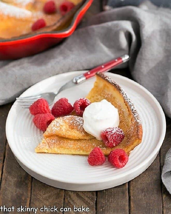 Best Dutch Baby Pancake slice on a white plate topped with cream and raspberries