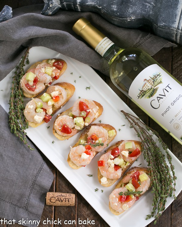 Greek Shrimp Crostini | Garlic toasts topped with shrimp, feta, tomatoes and more!
