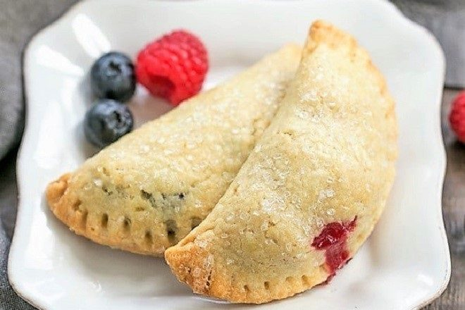 Rustic Berry Turnovers on a white plate with 3 berries