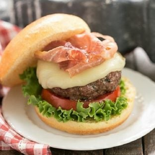 Italian Pesto Burger topped with cheese and prosciutto on a small white plate