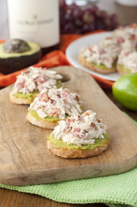 Avocado Chicken Salad Crostini on a wooden cutting board