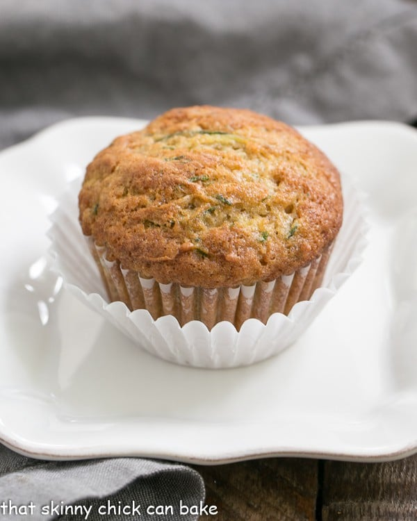 Cinnamon Zucchini Muffins on a white plate in a double white paper muffin wrapper