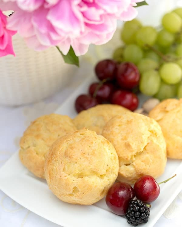 Triple Cheese Gougeres on a white tray with fruit