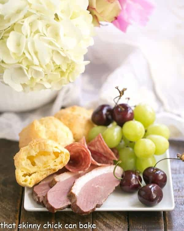 Triple Cheese Gougeres on a plate with charcuterie and fruit