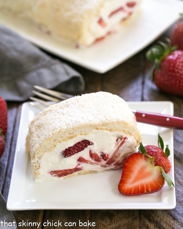 Strawberry Filled Meringue Roulade  slilce on a square white plate with a red handled fork and strawberry garnish
