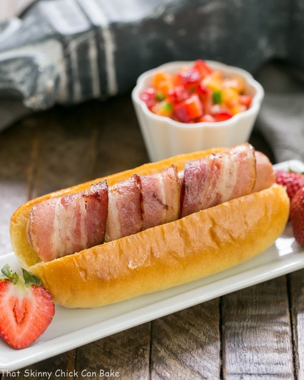 Bacon Wrapped Hot Dogs with Fruit Salsa on a rectangular plate with a ramekin of salsa