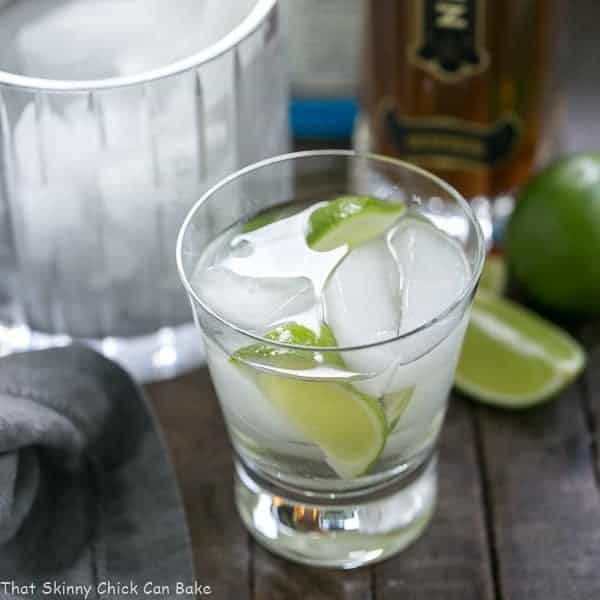 St. Germain Gin and Tonic Cocktail in a short glass with lime wedges