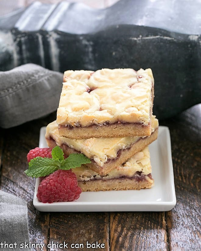 A stack of white chocolate raspberry bars on a square white plate with raspberries and mint to garnish