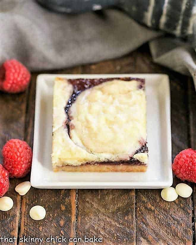 A White Chocolate Raspberry Bars on a white square plate