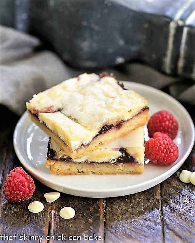 White Chocolate Raspberry Bars stacked on a round plate