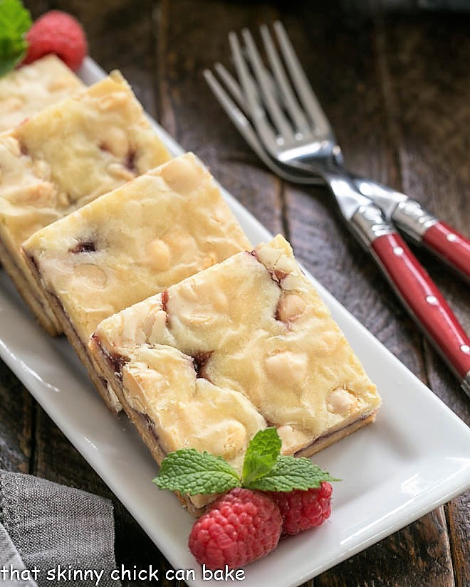 White choolate raspberry bars on a white tray with raspberries and mint