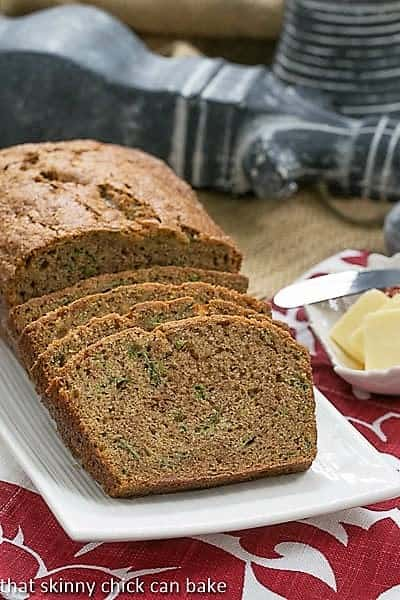 Classic Zucchini Bread loaf with slices on a white ceramic tray