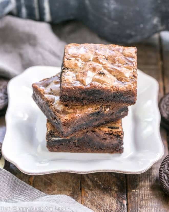 Stack of Chocolate Oreo Gooey Bars on a square white plate