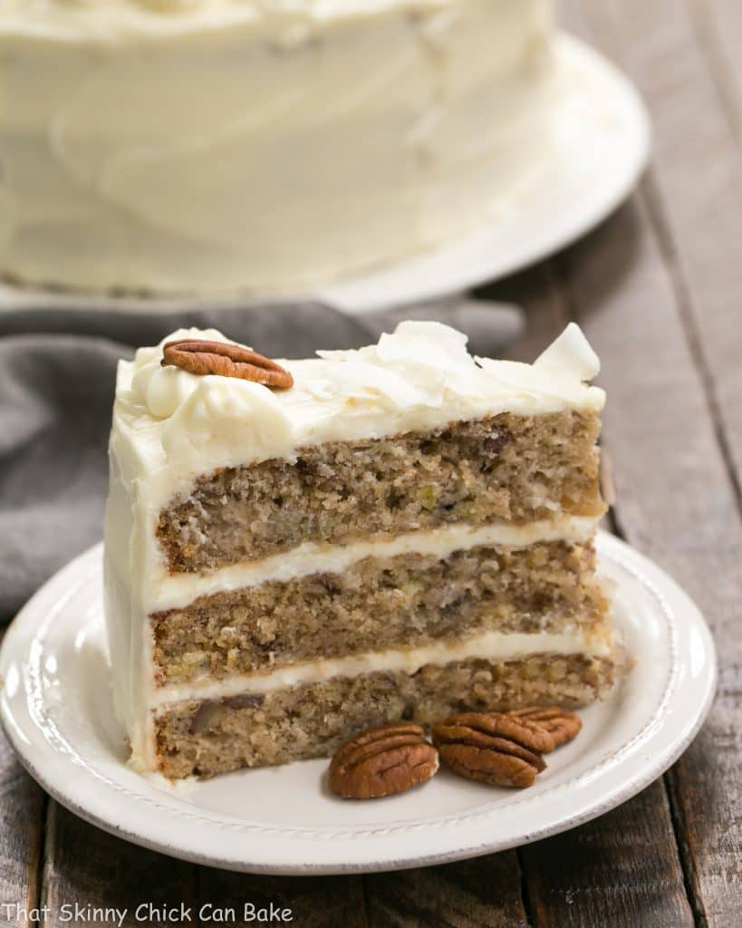 Classic Hummingbird Cake with Coconut | A dense, banana cake chock full of pecans, coconut and pineapple and slathered in cream cheese frosting!