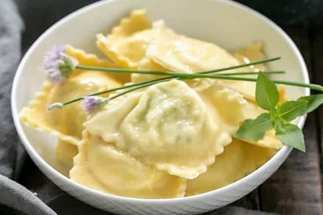 Bowl of Mozzarella, Basil, Parmigiano-Reggiano Ravioli with Butter Sage Sauce garnished with fresh basil and chives