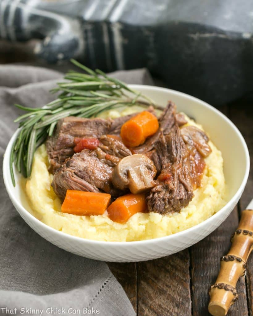 Pot Roast with Mushrooms, Tomatoes & Red Wine in a bowl with mashed potatoes