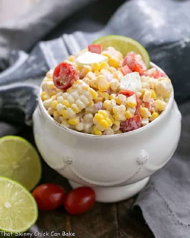 Spicy Mexican Corn Salad in a white tureen with limes and tomatoes