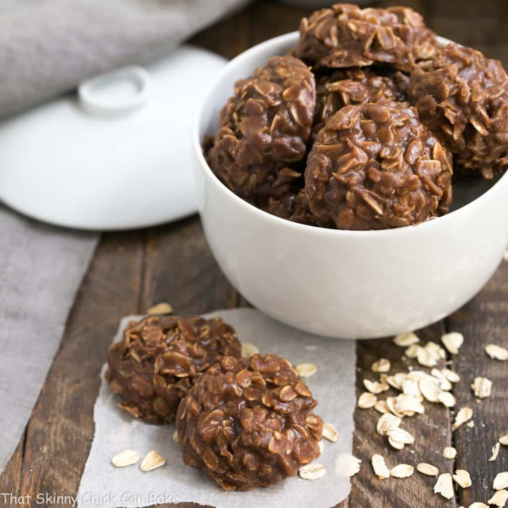 Classic Chocolate Peanut Butter No Bake Cookies in a white bowl with two cookies in the foreground