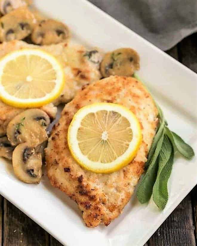 Creamy Chicken Marsala with Herbed Mushrooms topped with lemon slices on a white platter