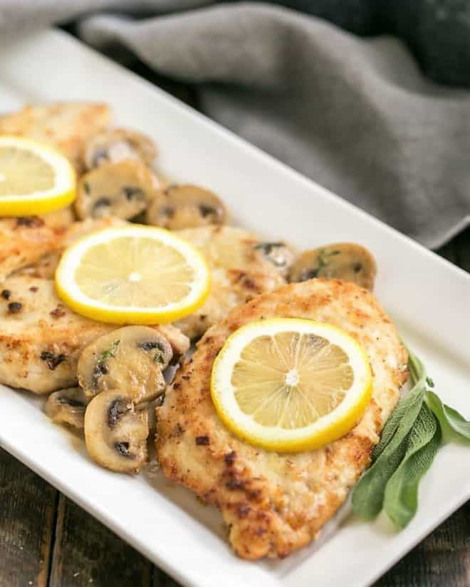 Creamy Chicken Marsala with Herbed Mushrooms on a white ceramic serving dish with lemons, mushrooms and sage