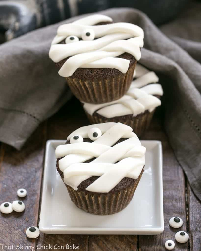 EASY Chocolate Mummy Cupcakes on a white plate and stacked with sugar eyes to garnish